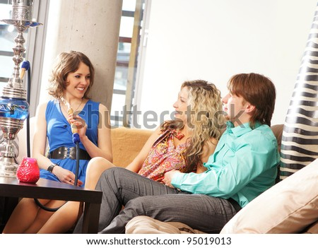 Group of young and sexy people smoking hookah in the lounge - stock photo