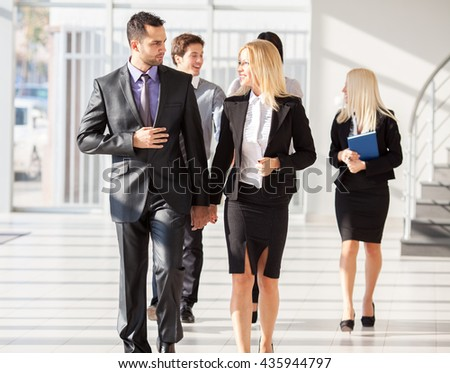 Group of young associates going to business meeting.They walking through lobby. - stock photo