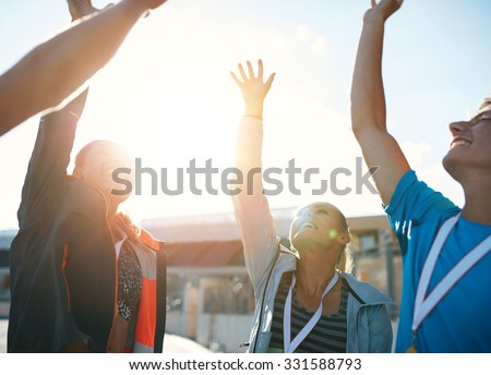 Group of young athletes celebrating success while standing in a huddle. Successful team of athletes cheering victory. - stock photo