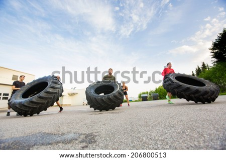 Group of young athletes doing tire-flip exercise outdoors - stock photo
