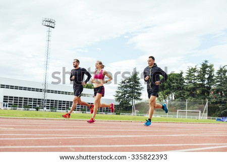 Group of young  athletics people running on the track field - stock photo