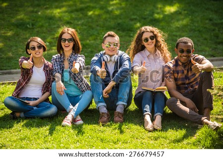 Group of young attractive smiling students dressed casual sitting on the lawn in park and resting. - stock photo
