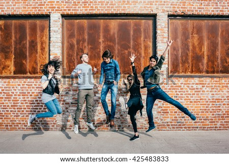 Group of young beautiful multiethnic man and woman friends having fun jumping outdoor in the city - happiness, friendship, teamwork concept - stock photo