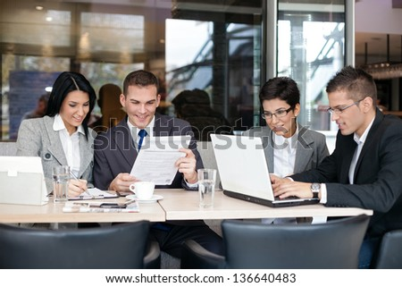 Group of young business people sitting at a table  and discussing an interesting idea in the cafe - stock photo
