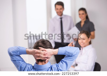 Group of young business people talking on business meeting. back view of man sitting at meeting in office  - stock photo
