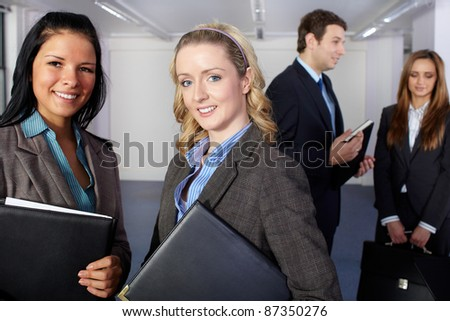 Group of 4 young business people, two females at foreground and two people blurred in the background - stock photo