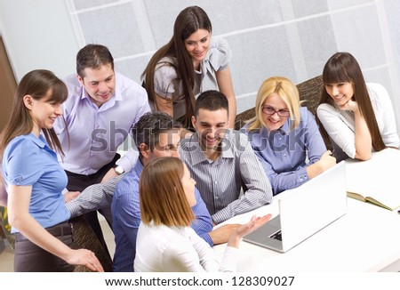 Group of young business people working in the office on laptop and discussing work - stock photo