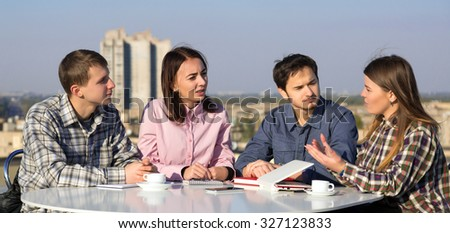 Group of Young Casual Dressed People on Informal Business Meeting at White Rounded Table Roof Top Cafe Terrace Urban Landscape Background - stock photo