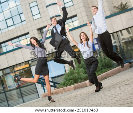 Group of young cheerful business people in front of office building, photographed at the moment of the jump. - stock photo