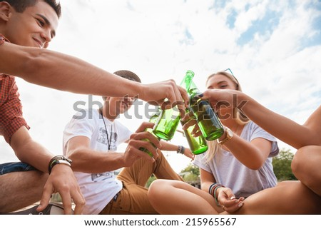 Group Of Young Cheerful People Toasting Outdoors - stock photo