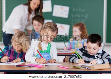 Group of young children studying in kindergarten school with focus to a little boy and two girls drawing with pencil crayons at the front as the teacher works with pupils at the back - stock photo