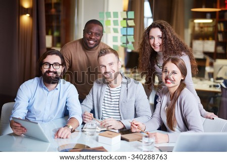 Group of young colleagues in casual looking at camera in office - stock photo