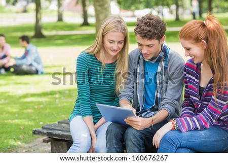 Group of young college students using tablet PC in the park - stock photo