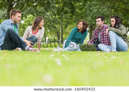 Group of young college students with laptop sitting in the park - stock photo