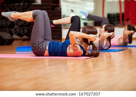 Group of young cute women working out and doing some crunches at a gym - stock photo