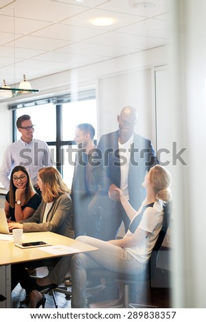 Group of young executives gathered and socializing in conference room - stock photo