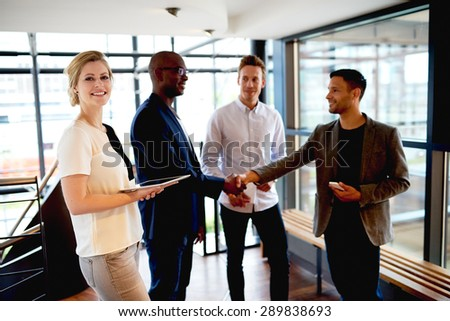 Group of young executives in modern space smiling and making introductions. - stock photo