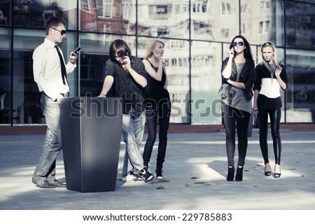 Group of young fashion men and women calling on the phones  - stock photo