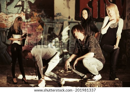Group of young fashion people at the graffiti wall  - stock photo