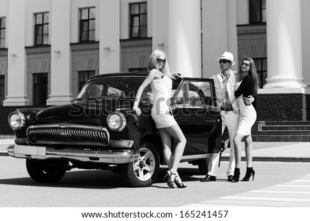 Group of young fashionable people at the retro car - stock photo