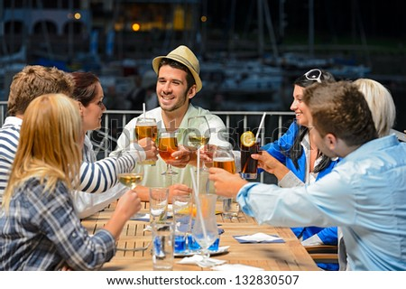 Group of young friends clinking their glasses celebrating night out - stock photo
