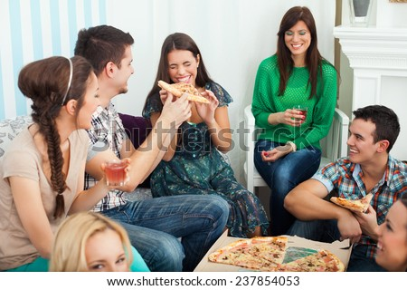 Group of young friends eating pizza indoors - stock photo