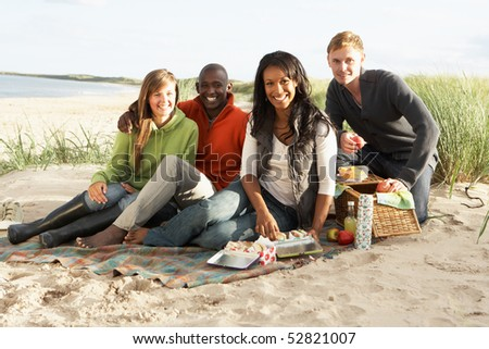 Group Of Young Friends Enjoying Picnic On Beach Together - stock photo