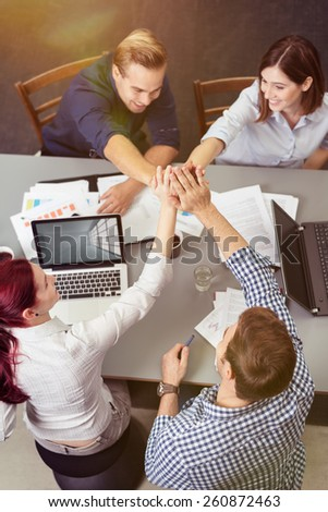 Group of Young Friends Having a Business Meeting at the Table with Laptops and Documents While Holding Their Hands Together at Center, Captured in Aerial View - stock photo