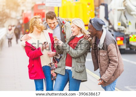 Group of young friends having fun in London. Mixed races people laughing and enjoying their time looking at a smart phone. Very candid and natural image with real expressions of happiness. - stock photo