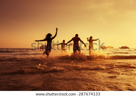 Group of young friends having fun on the beach - stock photo
