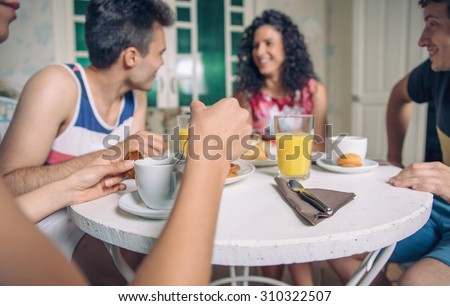 Group of young friends laughing and enjoying breakfast together at home. Focus on cup of coffee in the foreground. - stock photo