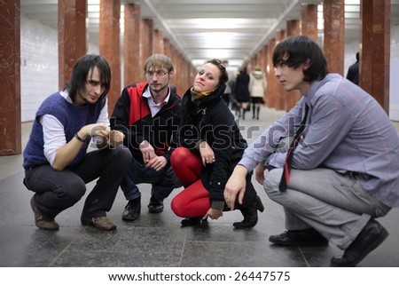 Group of young friends on subway station, focus on man in glasses - stock photo