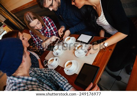 Group Of Young Friends Socializing In Cafe. - stock photo