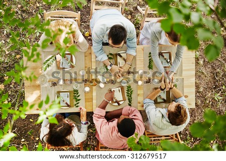 Group of young friends talking at Thanksgiving table - stock photo