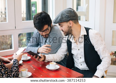 Group of young friends using cellphones while having a coffee in a cafe bar - stock photo
