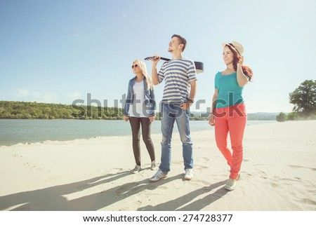 Group of young friends walking on the beach - stock photo