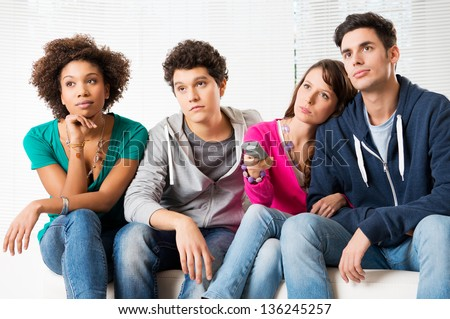 Group Of Young Friends Watching Television with bored expressions - stock photo
