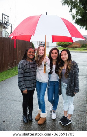 Group of young girl friends holding an umbrella in the rain - stock photo