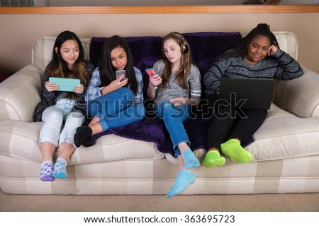 Group of young girls disengaged and distracted on mobile device - stock photo