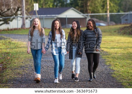 Group of young girls holding hands and laughing while walking on - stock photo