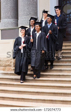group of young graduates walking down the stairs after ceremony - stock photo
