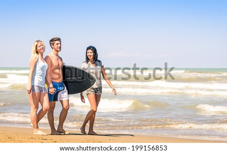 Group of young happy people on vacations at the beach holding a surf table - Best friends with girlfriends having fun in the summer with surfboard boogieboard during travel holidays - stock photo