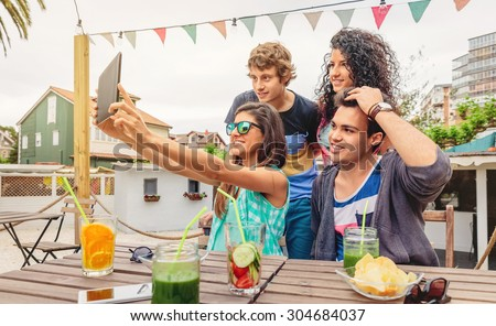 Group of young happy people taking a selfie with a electronic tablet in a summer party outdoors. Young people lifestyle concept. - stock photo