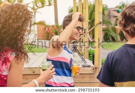 Group of young happy people with healthy drinks having fun in a summer party outdoors. Young people lifestyle concept. - stock photo