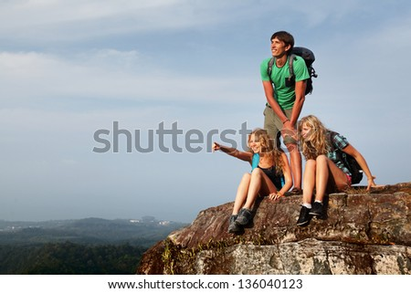 Group of young hikers relaxing on top of a mountain - stock photo