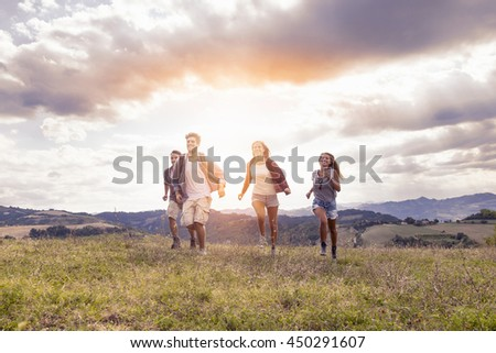 group of young hikers running toward the horizon over the mountain - stock photo