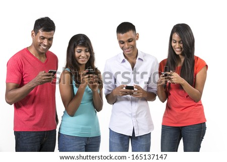 Group of young Indian friends using their smartphones. Happy Asian people using their cell phones. Isolated on white background. - stock photo