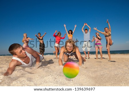 Group of young joyful people playing volleyball on the beach - stock photo