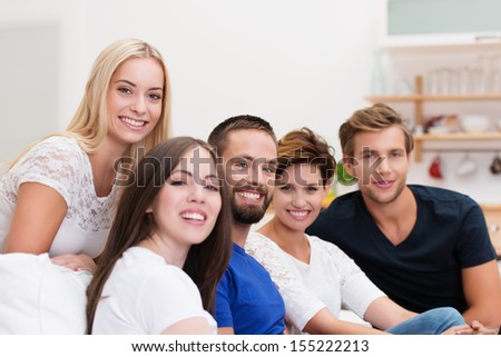 Group of young men and women relaxing at home on a living room sofa turning to smile at the camera with focus to a bearded young man in the centre - stock photo