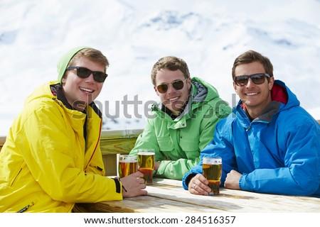 Group Of Young Men Enjoying Drink In Bar At Ski Resort - stock photo